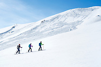 A group of ski tourers in Kyrgyzstan pass by a low angled slope that avalanched, a common, and dangerous issue when ski touring in the country
