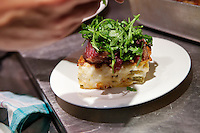A lasagne topped with beef carpaccio and rocket is prepared in the kitchen of restaurant 'Chat Noir, Chat Blanc', Nice, France, 10 April 2012