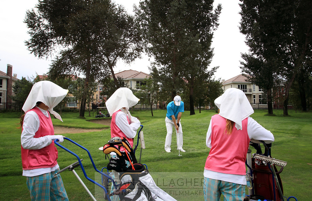 CHINA. Female caddies wait for a golfer to play his shot at Huatang International Golf Club in Beijing. 2009