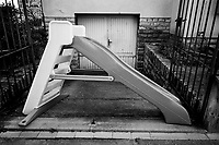 """Switzerland. Canton Ticino. Lugano. A plastic children slide in front of the garage of a private house. Nobody in the streets. Due to the spread of the coronavirus (also called Covid-19), the Federal Council has categorised the situation in the country as """"extraordinary"""". It has issued a recommendation to all citizens to stay at home, especially the sick and the elderly. 18.03.2020 © 2020 Didier Ruef"""