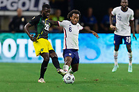 DALLAS, TX - JULY 25: Kemar Lawrence #20 of Jamaica battle Gianluca Busio #6 of the United States battle for a ball during a game between Jamaica and USMNT at AT&T Stadium on July 25, 2021 in Dallas, Texas.