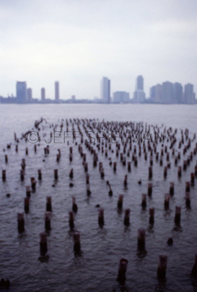 Original Image Photographed in 2003 on Color Transparency Film.  Please contact Jeff (click on contact) to license or purchase a fine art print of this image<br /> <br /> Soft Focus View of Wooden Posts (from an abandoned former pier) in the Hudson River, Lower Manhattan, New York City on an overcast afternoon, with Jersey City, New Jersey in the distance.<br /> <br /> Lower Manhattan, New York City, New York State, USA