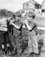 """- """"Twin boys and friend eating ice cream cone, Edmonton""""<br /> <br /> Photograph by Vernon Barford. From the Barford family fonds, A11484, ca. 1913."""