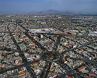 aerial photograph of the Plaza Africa roundabout (Glorieta Plaza Africa) in the Romero Rubio neighborhood of Mexico City, Mexico with the Mexico City International Airport in the background