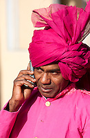 Jaipur, Rajasthan, India.  Guard at Entrance of City Palace Listening to Cell Phone prior to a Wedding Reception.