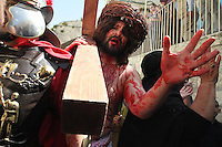 A Catholic pilgrim participates in the Passion Play, re-enacting the last walk of Christ as he and pilgrims of a Catholic ministry, Christ In You, The Hope of Glory, walk through the stations of the Via Dolorosa, traditionally believed to be Christ's route to crucifixion, in Jerusalem's Old City Friday March 29, 2013. Thousands of Catholic Christians are in Jerusalem to celebrate Good Friday in the city traditionally believed to be the place of Jesus' crucifixion and burial. Photo by Quique Kierszenbaum