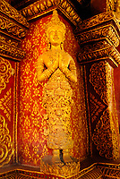 Small wooden statue of a prayer covered with gold on a wall corner on the library at Wat Phra Singh Buddhist temple in Chiang Mai city, Thailand, Southeast Asia. Construction on Wat Phra Singh began in 1345 when King Phayu, the fifth king of the Mangrai dynasty, had a chedi built to house the ashes of his father King Kham Fu.