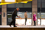 """© Joel Goodman - 07973 332324 . 16/12/2017. Manchester, UK. A night worker grits the ground at Exchange Square tram stop as temperatures drop to below freezing . Revellers out in Manchester City Centre overnight during """" Mad Friday """" , named for historically being one of the busiest nights of the year for the emergency services in the UK . Photo credit : Joel Goodman"""