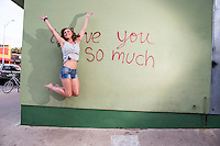 """Attractive Austin local woman jumps for joy at the """"i love you so much"""" mural on South Congress Ave. (SoCo)."""