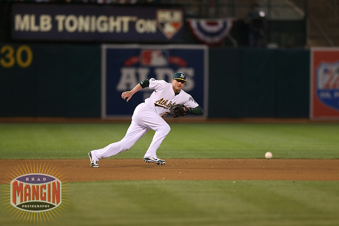 OAKLAND, CA - OCTOBER 11:  Josh Donaldson of the Oakland Athletics makes a play at third base during Game 5 of the ALDS against the Detroit Tigers at O.co Coliseum on October 11, 2012 in Oakland, California. (Photo by Brad Mangin)