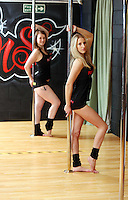 Pictured L-R: Tina Lediard and Sian O'Shea. Saturday 22 February 2014<br /> Re: Eight women have attempted to set a new world record of most people pole dancing at the same time.<br /> Pole 4 Life world record attempt was organised by Lisa Broughton at her Pole Twisters dance studio in Cardiff.<br /> The women had to pole dance for six minutes to set the new record.