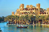 Dubai.  Madinat Jumeirah, the souk complex with waterside and rooftop restaurants and bars and windtowers.  Abra, water taxi..
