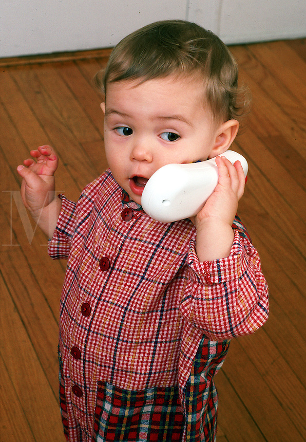 Toddler speaks on a portable telephone.