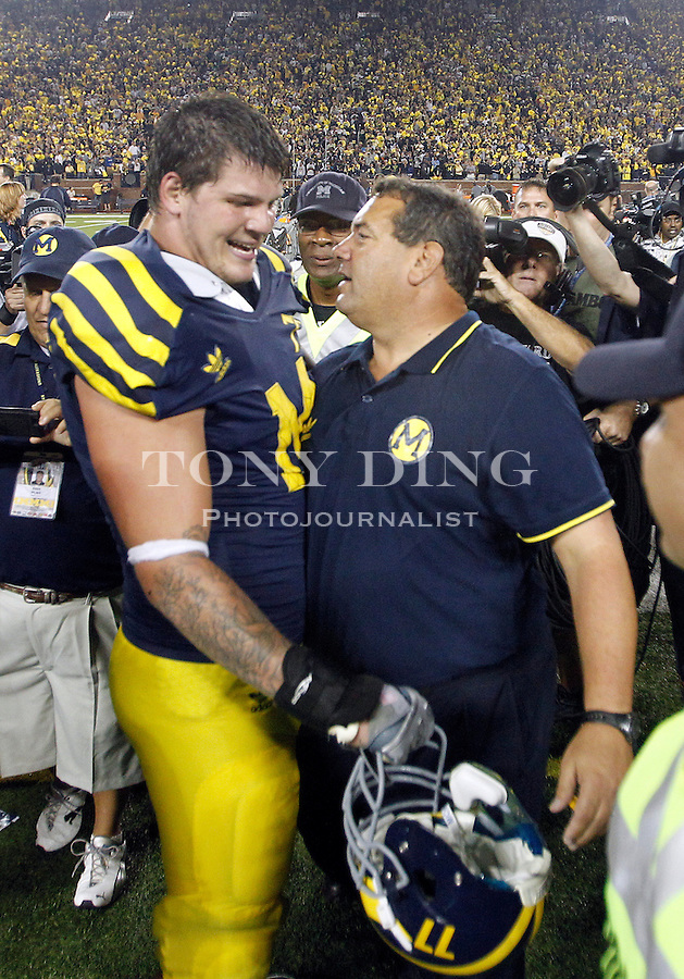 Michigan offensive lineman Taylor Lewan (77) gets a hug and celebrates with head coach Brady Hoke, right, after an NCAA college football game against Notre Dame, Saturday, Sept. 10, 2011, in Ann Arbor. Michigan won 35-31. (AP Photo/Tony Ding)