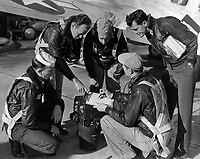 Students receiving instructions in photography.  Class 3, Aerial Photography students preparing to take off on a mapping flight.  Instructor E.R. Lang, PhoM 2/c, is explaining to the three students.  Pilot to right of picture is Lt. (jg) thomas C. Evans. Camera shown is a K-17 mapping camera with 12 inch lens.  In background is an SNB.