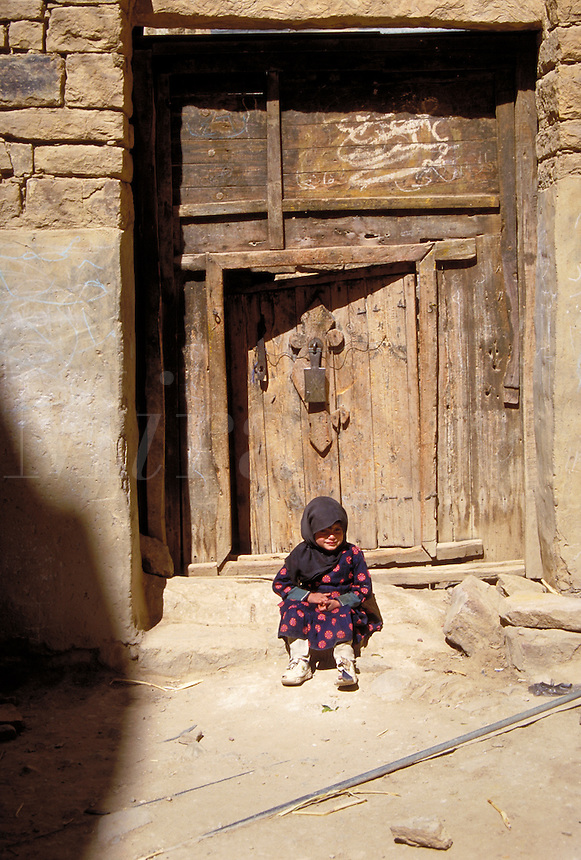 A little girl in tradtional Arabic dress (and sneakers) sitting on an old doorstep. Behind her is a heavy wooden door with a large, ornamental doorknocker. Thilla, Yemen.