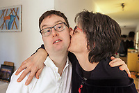Switzerland. Canton Ticino. Gordola. Simone Lunardi with his mother Giovana in their flat's living room. The mother kisses her loving son on the cheek. Simone Lunardi is a dancing member of MOPS_DanceSyndrome which is an independent Swiss artistic, cultural and social organisation operating in the field of contemporary dance and disability. It is composed only of Down dancers. Down syndrome (DS or DNS), also known as trisomy 21, is a genetic disorder caused by the presence of all or part of a third copy of chromosome 21 It is usually associated with physical growth delays, mild to moderate intellectual disability, and characteristic facial features. Gordola is a municipality in the district of Locarno. 31.01.2020 © 2020 Didier Ruef