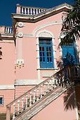 Ilheus, Bahia State, Brazil. Colonial school building painted pink with decorative detail of a cacu (coca) pod, in Praca Castro Alves.