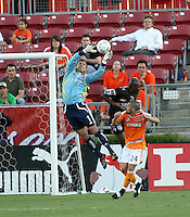 Houston Dynamo goalkeeper Zach Wells (1) makes the save as FC Pachuca defender Aquivaldo Mosquera (3) and Houston Dynamo defender Wade Barrett (24) attempt to make plays on the ball .   Houston Dynamo beat FC Pachuca 2-0 at Robertson Stadium in Houston, TX on March 15, 2007 in the first of a two game series in the CONCACAF Champions' Cup semi-finals.