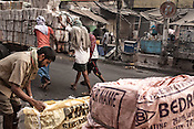 Day wage labourers push a big cart of daily newspaper to be distributed in Kolkata in West Bengal, India.
