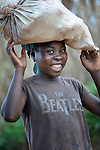 Carrying a bag on her head, a young woman walks along a road in the mountainous community of Foret-des-Pins, Haiti.
