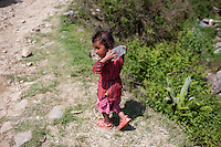 A child carries a bottle of drinking water  from a fountain in the village of Sudal, outside of Kathmandu, Nepal. May 05, 2015