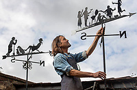 """BNPS.co.uk (01202 558833)<br /> Pic: ZacharyCulpin/BNPS<br /> <br /> Pictured: Graham with personal weather designs. Graham said """"Sometimes people send me pictures of their family so I can create them in the weathervane.<br /> <br /> Something in the wind..<br /> <br /> While Covid caused much of the world to slow down, business has been booming for weathervane maker Graham Smith.<br /> <br /> The former precision engineer has been so busy he has been working seven days a week and has had to close his books to new orders.<br /> <br /> Graham hand-crafts all his weathervanes, creating intricate designs and can even recreate families or significant events.<br /> <br /> With people stuck at home in lockdown and looking at DIY and home improvements, he said he has had his busiest year."""
