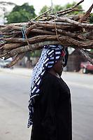 Zanzibar, Tanzania.  Lady carrying firewood on head.