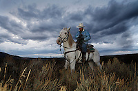 Under stormy evening skies, Edgar Oscanoa rides Dot trailing sheep in Upper Gully .<br />