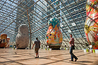 Moscow, Russia, 15/06/2011..People walk through an exhibition of of giant Russian matryoshki, or nesting dolls, in the newly-opened Afimall shopping centre. The dolls, designed by Boris Krasnov, are from 6 to 13 metres high, and each is decorated in a different style of traditional Russian folk art..Left - right: Fedoskono, Russian Imperial porcelain, Vologodskoe lacework, Mstero, and Ornamental Zhostovo painting styles.