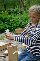 Kinder basteln sich einen Apfeltrockner, Mädchen trägt Holzleim auf, Apfel, Äpfel, Äpfel trocknen, Trockenobst, Apfelringe, apple, apples