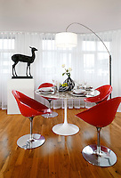 A contemporary dining room with a polished wood floor is furnished in retro style including four red Philippe Starck dining chairs and an Eero Saarinen white Tulip dining table