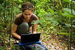 African Golden Cat (Caracal aurata aurata) biologist Laila Bahaa-el-din reviewing camera trap images on computer, Lope National Park, Gabon