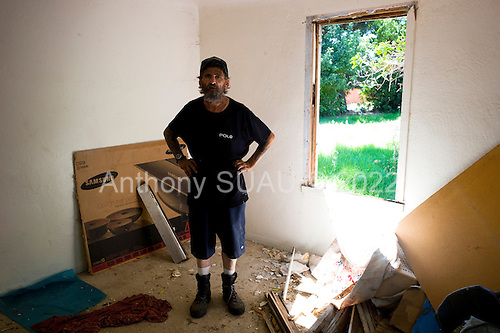 Modesto, California<br /> July 9, 2012<br /> <br /> John, an unemployed and homeless truck driver, hopes to clean up this room in an abandoned foreclosed home to sleep in. <br /> <br /> According to RealtyTrac, an online service that markets foreclosed properties, Modesto had the nation's third-highest home foreclosure rate during the third quarter of 2010, just behind Las Vegas, Nevada, and Cape Coral/Fort Meyers, Florida. <br /> <br /> They are pretty easy to spot: Amid the neatly manicured lawns and landscapes of Modesto's streets, foreclosed homes are the ones where the lawn has gone feral, the shades in the windows sit askew, and rows of legal notices are taped to the windows near the front door.
