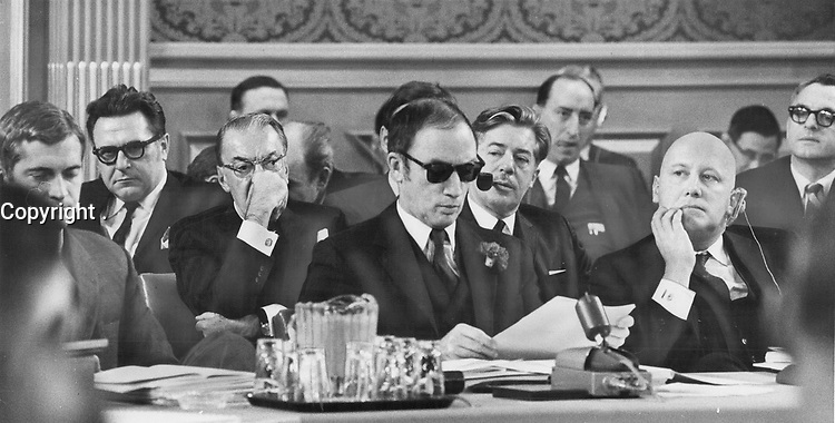 Wearing sunglasses he went home to pick up at launchtime to shield his eyes from the glare of TV lights; Prime Minister Pierre Trudeau reads a statement at yesterday's federal-provincial conference. Sitting beside him; from left; Justice Minister John Turner; Immigration Minister Allan MacEachen; Senator Paul Martin; Trudeau; Manpower Minister Jean Marchand; Marc Lalonde; Assistant to Prime Minister; and Consumer Affairs Minister Ron Basford.<br /> <br /> Griffin, Doug<br /> Picture, 1969,