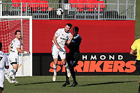 RICHMOND, VA - SEPTEMBER 30: Conor Donovan #20 of North Carolina FC and Omar Sowe #67 of New York Red Bulls II challenge for a header during a game between North Carolina FC and New York Red Bulls II at City Stadium on September 30, 2020 in Richmond, Virginia.
