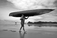 Fisherman lugging his canoe back to safety during low tide in Jaque, Panama.