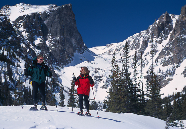 A couple snowshoeing near Bear Lake beneath Hallett Peak in Rocky Mountain National Park Colorado