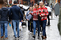 A man and a woman with matching Christmas jumpers join other last minute Christmas shoppers in Oxford Street, in the city centre of Swansea, Wales, UK. Sunday 24 December 2017