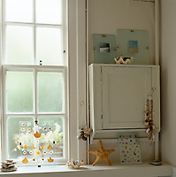 The bathroom is decorated with shells, pebbles, a starfish and pressed leaves
