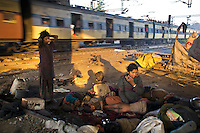 A mother and her children wake upon waste ground beneath a flyover near Okhla station as a train travels past.