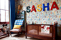 Papier-mache letters from Edit58 spell out the child's name on 'Alice in Wonderland' wallpaper, a 30's design by CFA Voysey