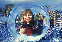 Young girl looks through ice lens at the World Ice Art Championships in Fairbanks, Alaska.
