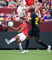 Nani (17) of Manchester United crosses the ball over Eric Abidal (22) of Barcelona during the friendly at FedEX Field in Landover, MD.  Manchester United defeated FC Barcelona, 2-1.