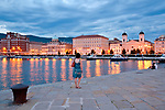 Standing on the Molo Audace pier, looking towards downtown at sunset in Trieste, Italy