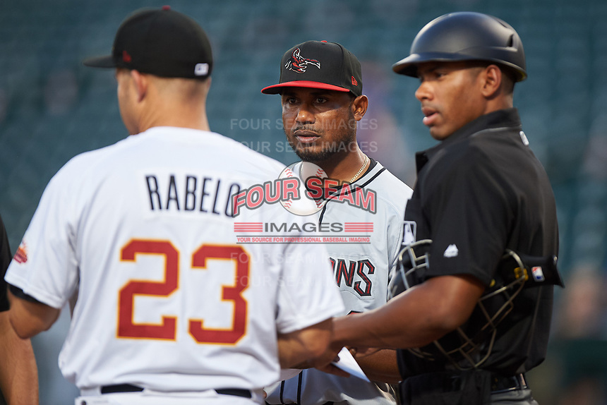 Scottsdale Scorpions manager Cesar Martin (14) meets with Mesa Solar Sox manager Mike Rabelo (23) and home plate umpire Edwin Moscoso during the lineup exchange before an Arizona Fall League game on September 18, 2019 at Sloan Park in Mesa, Arizona. Scottsdale defeated Mesa 5-4. (Zachary Lucy/Four Seam Images)