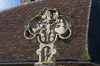 Croix sculptée qui, d'après le costume du chevalier en prière, pourrait dater de la fin du 14e ou du début du 15e siècle. Sur la face est, un Christ en croix est entouré de quatre anges aux ailes déployées, portant des calices. En-dessous, dans une petite niche, un chevalier revetu de l'armure, la tete relevee vers la croix, coiffe d'un casque, est a genoux, en priere. La face ouest represente une Vierge en gloire entouree d'anges. La colonne qui supporte la croix ainsi que le socle ont ete refaits et portent la date de 1883