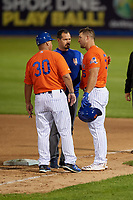 Syracuse Mets Tim Tebow (15) gets looked at by Coach Benny Distefano (30) and Athletic Trainer Grant Hufford after being hit in the head by a pitch during an International League game against the Charlotte Knights on June 11, 2019 at NBT Bank Stadium in Syracuse, New York.  Syracuse defeated Charlotte 15-8.  (Mike Janes/Four Seam Images)