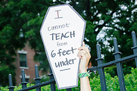 """A demonstrator holds a sign reading """"I cannot teach from 6 feet under"""" as people gathered outside the Massachusetts State House for a protest organized by the Massachusetts Teachers Association against current school reopening plans during the ongoing Coronavirus (COVID-19) global pandemic in Boston, Massachusetts, on Wed., Aug. 19, 2020. The teachers' union, alongside two other Massachusetts teachers' unions, organized the event as part of a mass day of action demanding that the school year starts with remote learning and switch to in-person learning only when health and safety standards can be guaranteed."""