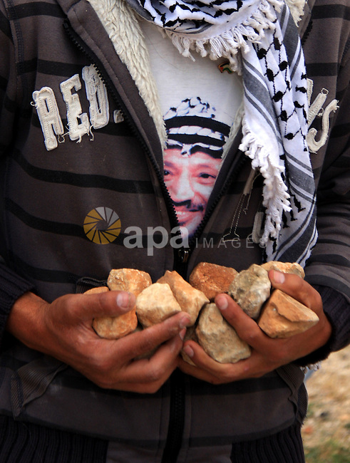 """A Palestinian youth holds stones to be thrown at Israeli forces during a protest against Israel's controversial separation barrier and to mark the 63th anniversary of """"Nakba"""" (catastrophe) on May 13, 2011in the West Bank village of Bilin. Nakba means """"catastrophe"""" in reference to the birth of the state of Israel 63 years ago in British-mandate Palestine, which led to the displacement of hundreds of thousands of Palestinians who either fled or were driven out of their homes during the 1948 war over Israel's creation. Photo by Wagdi Eshtayah"""